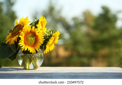Beautiful sunflowers on table on bright background