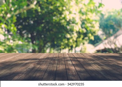 Beautiful sunlight in the autumn forest with wood planks floor, nature background, bokeh background