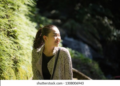 Beautiful sunlight over young woman face with lovely smile with green mos on stone wall at the side.