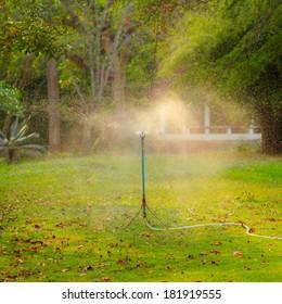 beautiful sunlight and water springer in garden