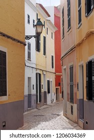 a beautiful sunlit narrow cobbled quiet street of old houses painted typical Mediterranean bright colors in ciutadella menorca spain