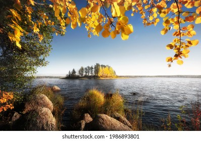 Beautiful sunny autumn island in frame of golden leaves and stones. Fall in Vyborg bay, gulf of Finland