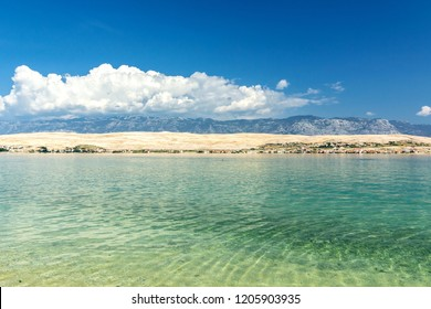 Beautiful sunny beach, blue water, mountains in the background