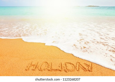 """Beautiful sunny beach by the blue sea. Word """"Holiday"""" written on the sand"""