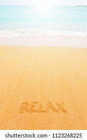 """Beautiful sunny beach by the blue sea. Inscription """"Relax"""" made on the sand"""