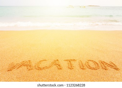 """Beautiful sunny beach by the blue sea. Inscription """"Vacation"""" made on the sand"""
