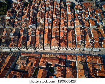 Beautiful sunny cityscape of old Dubrovnik with houses with shingled roofs and fortification walls in Croatia. People are walking on streets. Top view horizontal photo.