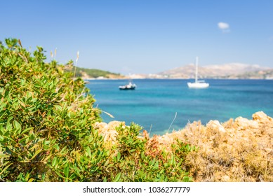 Beautiful sunny coast view to the greek blue sea with crystal clear water beach with some boats fishing cruising surrounded by hills mountains, Leros, Dodecanese Islands/ Greece
