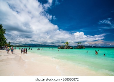 Beautiful sunny day at Boracay Island Philippines. White sand beach palms and blue sea ocean people walking along the beach