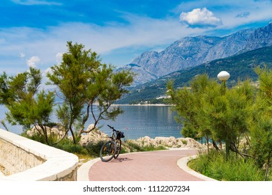 Beautiful sunny day in Makarska Croatia Europe, Nice outdoors of the popular tourist city in Dalmatia. Bicycle, Adriatic Sea and Mountains. Calm, peaceful and happy photo.