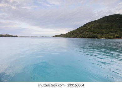 Beautiful Sunny Day Over The Caribbean Sea With Islands, Clouds, Blue Skies, Clear Blue Water, And Green Plants.