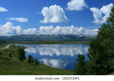 Beautiful sunny day overlooking the lake in the Altai Republic in Russia. White clouds in the blue sky reflected in the water and green trees