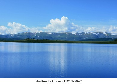 Beautiful sunny day overlooking the lake in the Altai Republic in Russia. White clouds in the blue sky reflected in the water and snow in the mountains far away on the horizon
