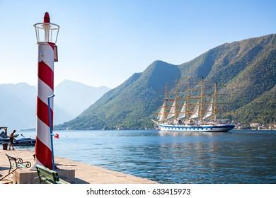 Beautiful sunny day in Perast, Montenegro, big sailing ship is entering the Kotor bay (Boka Kotorska), Montenegro, Europe, old historical town. Lighthouse.