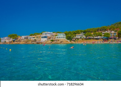 Beautiful sunny day in Sant Elm, with a beautiful blue water in Majorca, with some building in the horizont and people enjoying the weather, in Spain