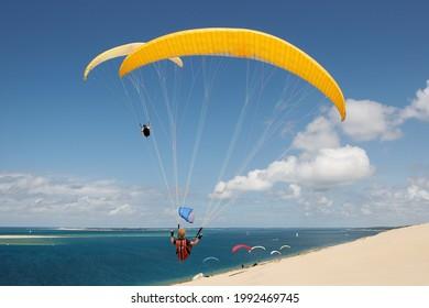 Bel paysage ensoleillé avec quelques nuages de la dune de Pyla avec deux parapents volant en gros plan