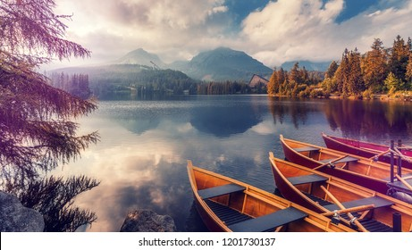 Beautiful sunny landscape. View on mountain lake with crystal clear azure water in High Tatras. Slovakia. Red Boats on the water glowing in sunlight at sunset. Awesome Autumn landscape. Strbsce pleso