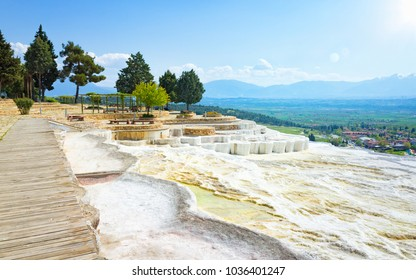Beautiful sunny morning with blue sky and mountain on horizon in Pamukkale. White travertine terrace formations left by flowing water in Pamukkale, Denizli Province in southwestern Turkey.