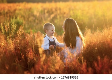 Beautiful sunny photo of motherhood, Caucasian mom with long hair in summer at sunset in the grass with her son toddler. Back light, soft focus and toning