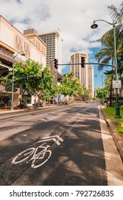 Beautiful sunny street of Honolulu, Hawaii with many plants, bike lane and traffic lights.