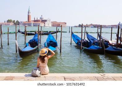 Beautiful sunny Venice-girl sitting on the pier, near the gondola.