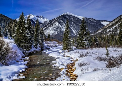 Beautiful sunny winter morning with mountain peaks covered with freshly fallen snow and river running up the valley in a snow covered alpine forest