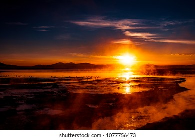 Beautiful Sunrise against hazy vapors from thermal lake and flamingos, Salar de Uyuni, Bolivia, Latin America