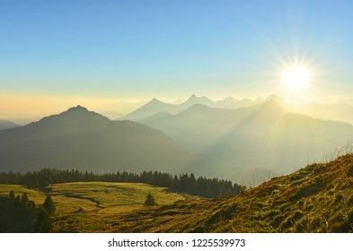 Beautiful sunrise in the Allgaeu Alps at the border region of Germany and Austria. Silhouettes of mountains and mountain ranges with orange and blue sky. Sun in backlight. Copy space.