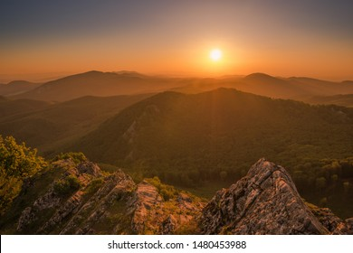 Beautiful sunrise from behind the horizon in the mountains with a cloudless sky