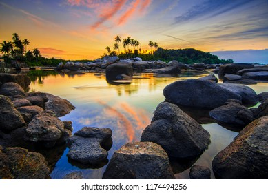 Beautiful sunrise between the beach rocks of Trikora island of Bintan