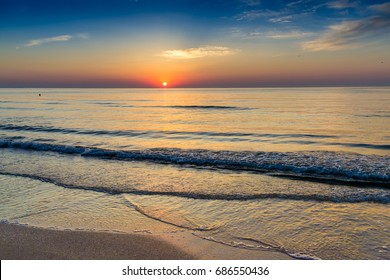 Beautiful sunrise of the Black Sea shot in Mamaia tourist resort in Romania. Vivid colors showing up at the horizon while waves hitting the shore