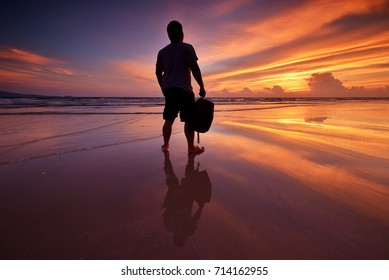 Beautiful sunrise, blue sky and silhouette of men standing on the beach