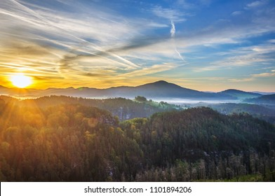 Beautiful sunrise at Bohemian Switzerland National Park in Czech republic. Colored sky during daybreak in Czech Switzerland region. Landscape photo of autumn colourful trees, hill and fog in valley.