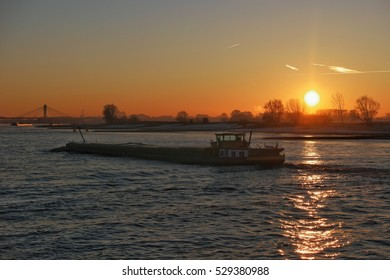 beautiful Sunrise by the Waal River with the bridge of Ewijk on the background and inlandships sailing over the river by Nijmegen Netherlands 5 December 2016  binnenvaart Sunrise inland shipping,