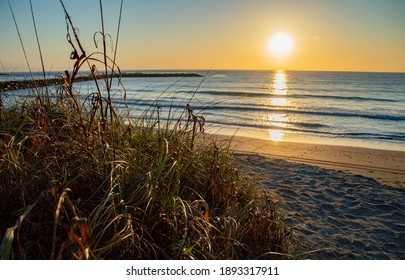 Beautiful sunrise captured on a summer morning in Florida. Calming waves and a jetty for fishing.