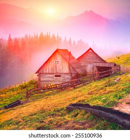 Beautiful sunrise in Carpathian mountains with nature wooden houses on a forest hill.