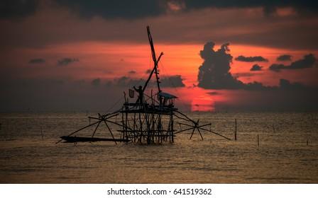 Beautiful sunrise and fisherman working on his fishing gear at Pakpra.