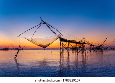 Beautiful sunrise and fishing dip nets at Pakpra in Phatthalung, Thailand.