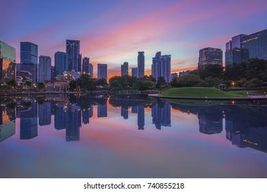 Beautiful sunrise at Kuala Lumpur city skyline with perfect reflection on the lake surface