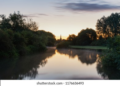 Beautiful sunrise landscape image of River Thames at Lechlade-on-Thames in English Cotswolds countryside with church spire in background
