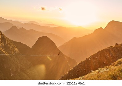 Beautiful sunrise landscape on the canyon mountais, with a silhouette of man doing slack line over the gap, extreme sports, balance, adrenaline, golden hour
