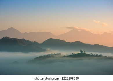 Beautiful sunrise landscape of Saint Thomas Church in Slovenia on hilltop in the morning fog with orange and blue sky and Triglav mountain background
