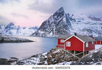 Beautiful sunrise landscape with traditional Norwegian fishing huts in the mountains of Lofoten islands in Norwegian Sea, Norway