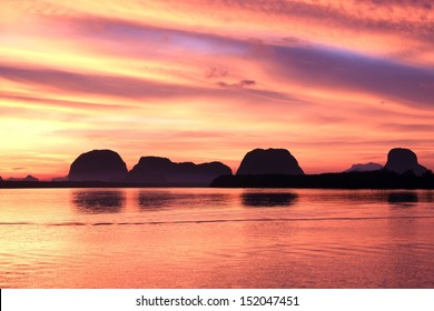 Beautiful sunrise in local sea with Silhouette mountains background in Phang Nga , Thailand