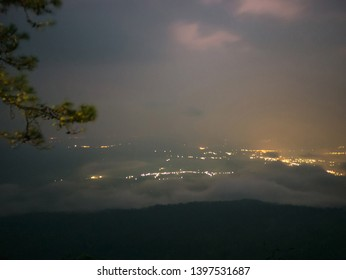 Beautiful sunrise with Loei City light and sea of mist in the early morning on Phu Kradueng mountain national park in Loei City Thailand.Phu Kradueng national park the famous Travel destination