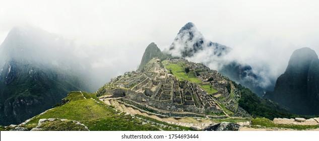 Beautiful sunrise from Machu Picchu ruins in Peru on a foggy day