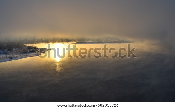 beautiful sunrise and mist over the river in winter