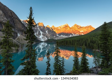 Beautiful sunrise at the Moraine lake with snow-covered rocky mountains in Banff National Park, Canada.