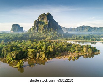Beautiful sunrise mountain landscape with fog and the lake photograph by drone photography, Krabi Province Thailand. Lime stone mountain in swamp of mangrove forest.