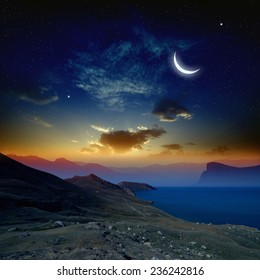 Beautiful sunrise in mountains and sea, glowing horizon, moon and bright stars in dark blue sky. Elements of this image furnished by NASA http://visibleearth.nasa.gov